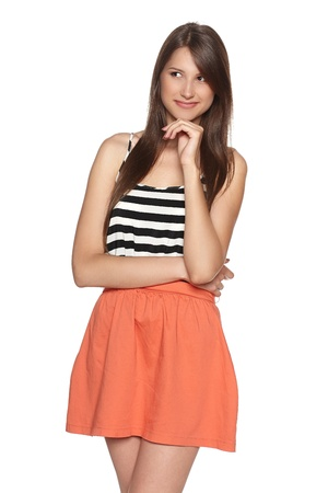 Young smiling female with hand on chin looking to the side, against white background Stock Photo