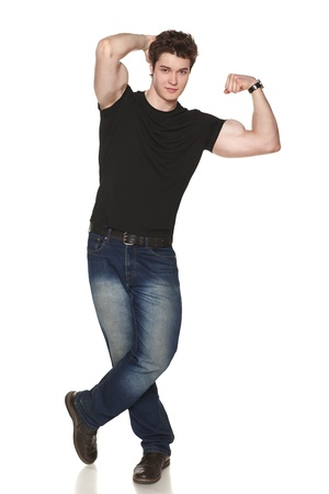 Smiling casual male in full length showing his muscles against white background photo