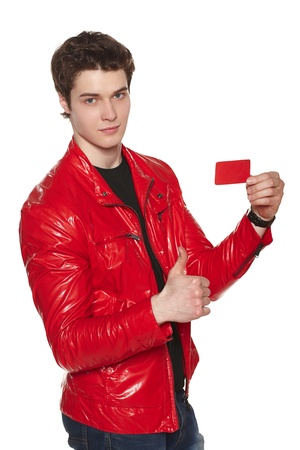 Young man wearing bright red jacket showing blank credit card, gesturing thumb up, over white background photo