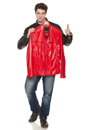 Young male wearing black jacket showing you red bright leather jacket, gesturing thumb up. Against white background photo
