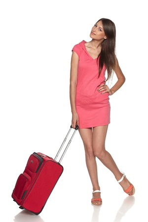 Casual teen girl with red suitcase in full length over white background photo