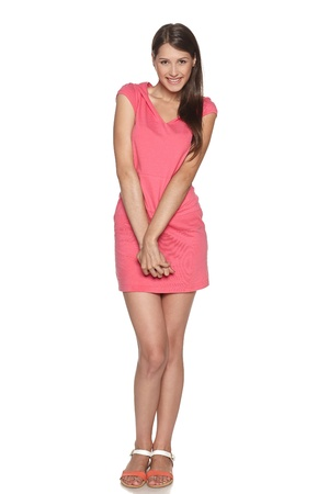 Full length of smiling young female feeling uncomfortable and shy isolated against a white background photo