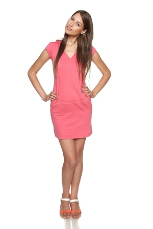 Smiling female wearing sport style pink dress posing with hands on hips,  isolated on white background photo
