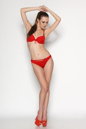Sexy woman in red bikini in full length posing