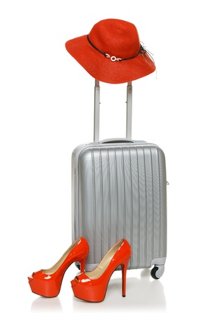 Silver suitcase with red straw hat on the handle and red high heel shoes near it, isolated on white background photo