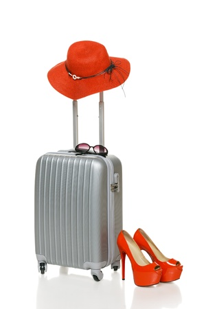 Silver suitcase with red straw hat, red high heel shoes and sunglasses, isolated on white background photo