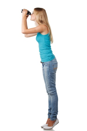 observation: Side view of full length blond woman looking through binoculars sideways Stock Photo