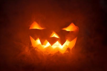 dynia: Straszny Dynia Halloween patrząc przez dym. Świecące, palenia monster dyni z głębi piekła