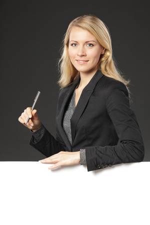 Young business woman standing behind and leaning on a white blank  holding a pen, over grey background photo