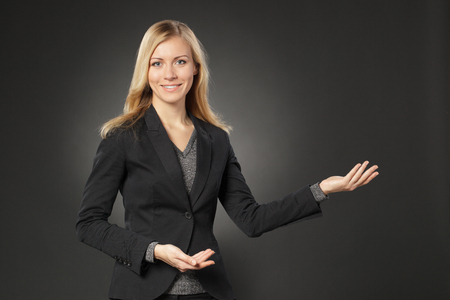 welcoming: Beautiful blond business woman showing copy space over grey background