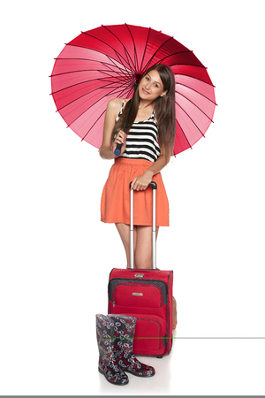 Smiling female under umbrella staning with suitcase, with rubber boots, in full length, over white background photo