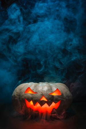 carved pumpkin: Smoking Halloween Pumpkin. Glowing, smoking monster pumpkin in dark. Stock Photo