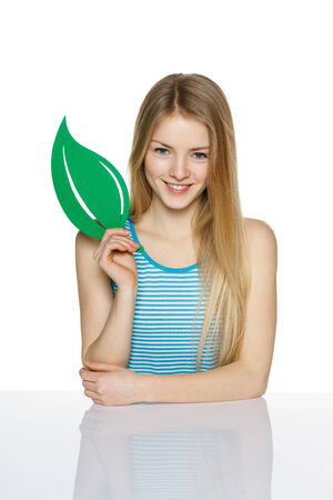 Young female holding eco symbol leaf, over white background Stock Photo - 23033021