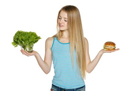 toma de decision: Mujer toma de decisiones entre la ensalada sana y la comida rápida, sobre fondo blanco Foto de archivo