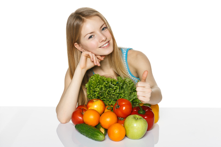 acclamation: Beautiful blond smiling girl sitting with vegetables and fruits  on table, showing thumb up fgesture, over white background