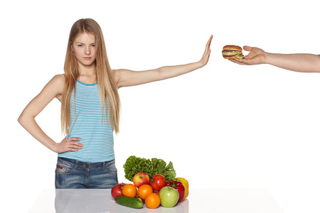 disinclination: Serious young female refusing fast food, against white background