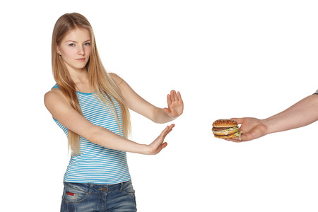 disinclination: Discontent young female refusing fast food, against white background