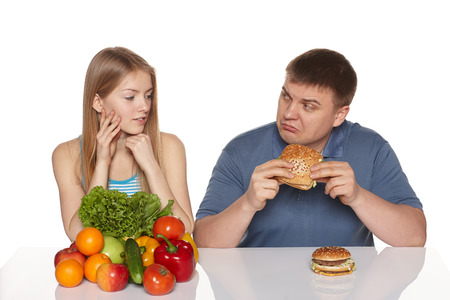 gobble: Choosing healthy eating concept  Woman looking whit dissaproval look as her boyfriend eating fast food, against white background Stock Photo