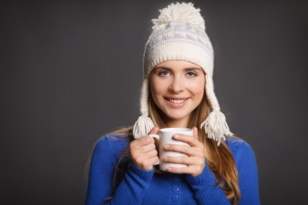 Winter woman wearing warm winter clothing: sweater and wool cap holding a snowflake, against gray background Stock Photo - 22578765