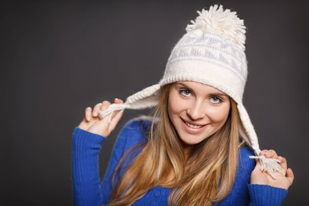 Playful winter woman wearing warm winter clothing - sweater and wool cap against gray background photo