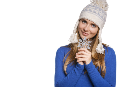 Winter woman wearing warm winter clothing: sweater and wool cap holding a snowflake, against white background photo