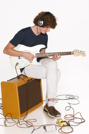 Full length redheaded male musician with his electric guitar sitting on the  guitar amplifier over white background