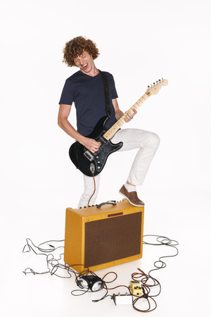 passionately: Male guitarist standing with one leg on a guitar amplifier and playing his guitar passionately, isolated on white