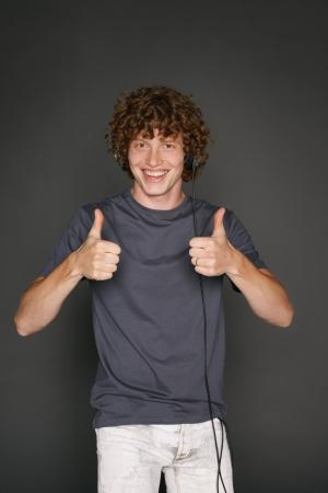 Hombre feliz en auriculares se�alando el pulgar hacia arriba, contra el fondo gris photo
