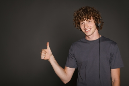 Happy male in headphones gesturing thumb up, against gray background photo
