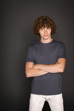 Portrait of curly redheaded serious man standing with folded hands over gray background photo