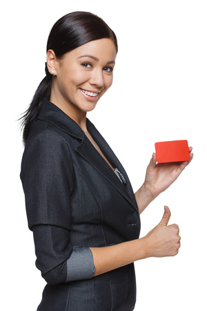 Smiling business woman showing credit card and gesturing thumb up,  isolated on white background