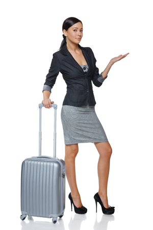 Businesswoman in full length with suitcase showing blank copy space  open hand palm, over white background photo