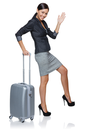 Funny image of a businesswoman in full length walking like a robot with suitcase, over white background photo
