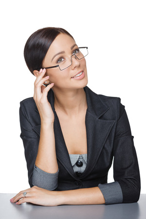hair tied: Smiling businesswoman sitting at table looking up at blank copy space, over white background Stock Photo