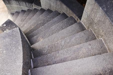 bajando escaleras: Redondeado escalera de piedra de fuga en la planta baja Foto de archivo