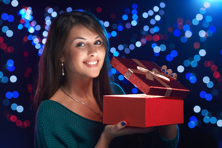 open gift: Happy girl opening Christmas box wich is glowing inside