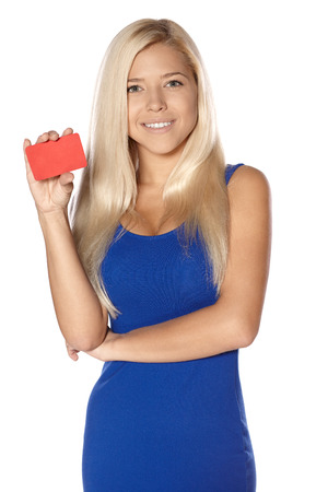 Smiling woman in blue dress holding credit card isolated on white background photo