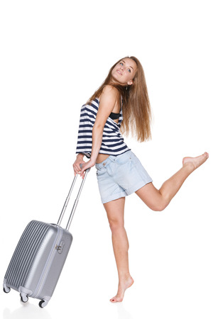 Excited teenager hipster with travel suitcase in full length looking to the side,  isolated on white background photo