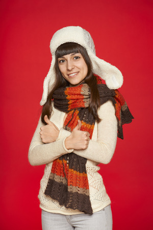 approvement: Winter girl in hat and muffler gesturing thumbs up over red background