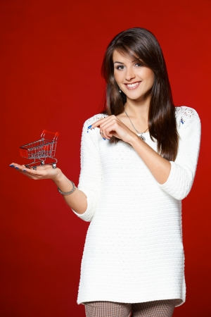 Smiling woman holding small empty shopping cart on her palm, and pointing at it, over red background photo
