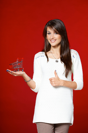 Smiling woman holding small empty shopping cart on her palm, and gesturing thumb up, over red background photo