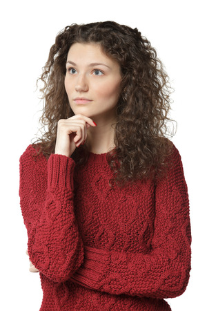 Portrait of young pensive female standing with folded hands and her hand on the chin looking sideways, over white background photo