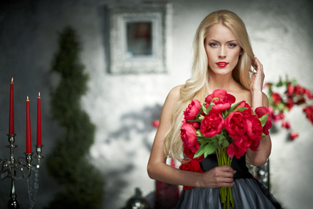 Closeup portrait of fashion model posing with bunch of peonies photo