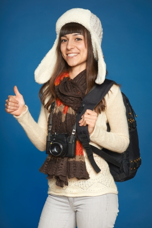 Winter girl in hat and muffler with photocamera and backpack over blue background  Happy female gesturing thumb up  Stock Photo