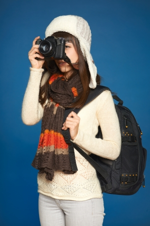 Winter girl looking through the photocamera viewfinder over blue background photo