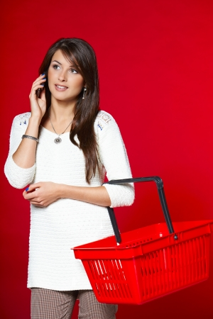 Young woman with red shopping basket, studio shot photo