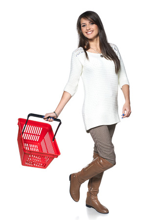 Full length woman walking with red shopping basket, white background photo