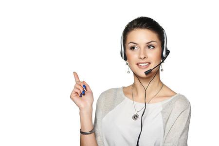 hands free: Operador de centro de llamada del auricular Telemarketing mujer sonriente que habla en las manos el dispositivo manos libres Bluetooth, apuntando hacia el lado en el espacio de la copia en blanco.