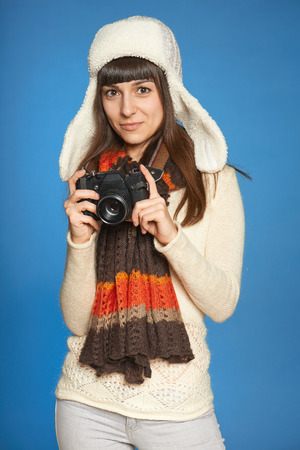 Woman photographer holding photo camera over blue  Stock Photo