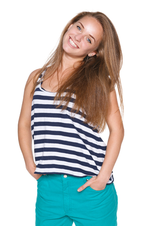 Enjoyment - Positive teen girl in casual summer clothes with hands in pockets , over white  photo